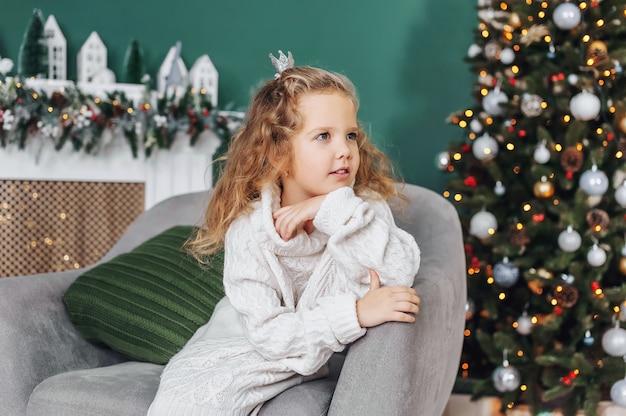 Kleines mädchen in einem pullover sitzt auf dem hintergrund der weihnachtsdekoration.