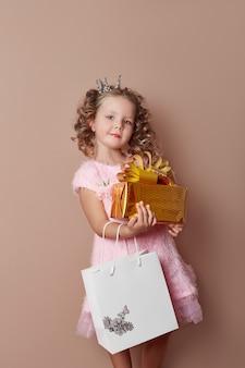 Kleines mädchen in einem rosa kleid hält eine goldene geschenkbox in den händen und ein paket. das mädchen geht einkaufen, einkaufszentrum und kauft geschenke für den urlaub. russland, swerdlowsk, 10. januar 2019