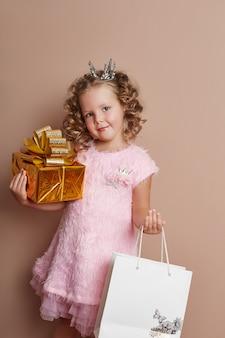 Kleines mädchen in einem rosa kleid hält eine goldene geschenkbox