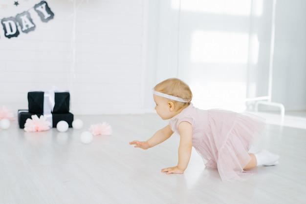 Kleines mädchen in einem rosa kleid kriecht auf dem boden
