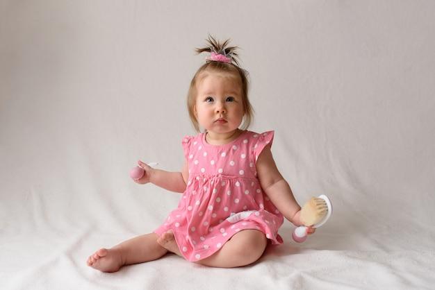 Kleines mädchen in einem rosa kleid sitzt mit einem kamm in der hand auf einer weißen oberfläche