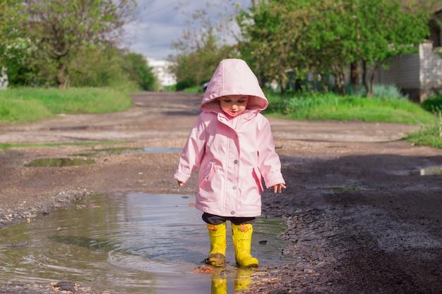 Kleines mädchen in einem rosa regenmantel und gelben gummistiefeln geht in eine pfütze