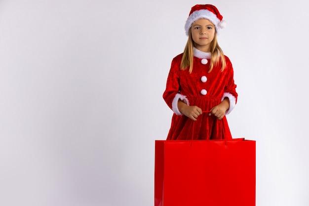 Kleines mädchen in einem roten kleid und in einer roten weihnachtsmannmütze, mit einer geschenktüte in ihren händen.
