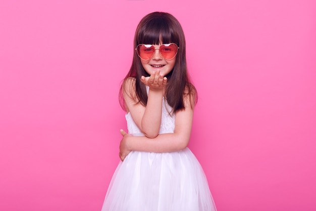 Kleines mädchen in einem schicken weißen kleid und einer herzförmigen brille schaut nach vorne, lächelt und sendet einen luftkuss, der positive gefühle ausdrückt, isoliert über rosa wand