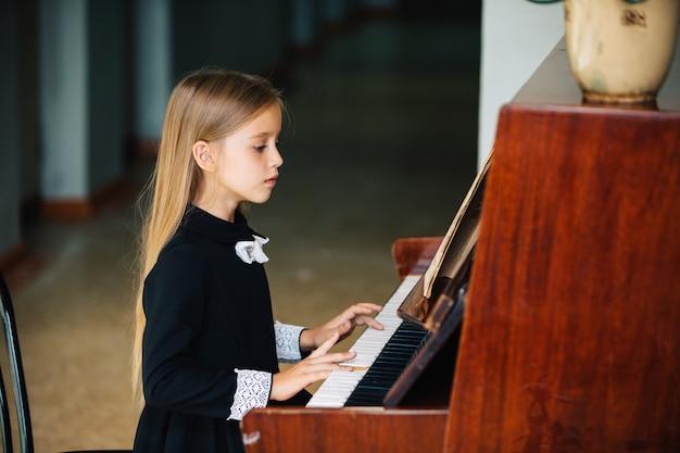 Kleines mädchen in einem schwarzen kleid lernt, klavier zu spielen. das kind spielt ein musikinstrument.