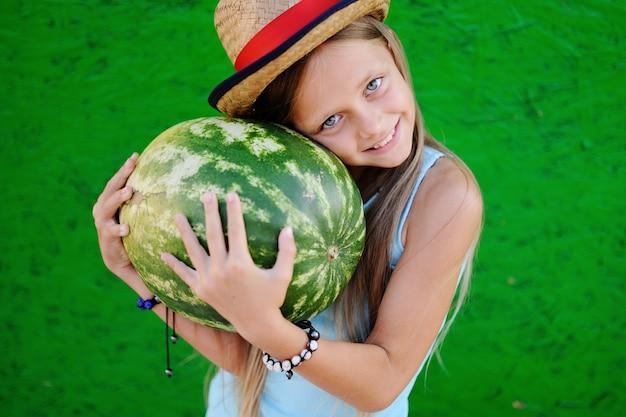 Kleines mädchen in einem strohhut mit wassermelone in seinen händen auf einem grünen hintergrund