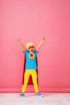 Kleines mädchen in einem superheldenkostüm in rotem umhang und hut zeigt, wie stark sie ist.