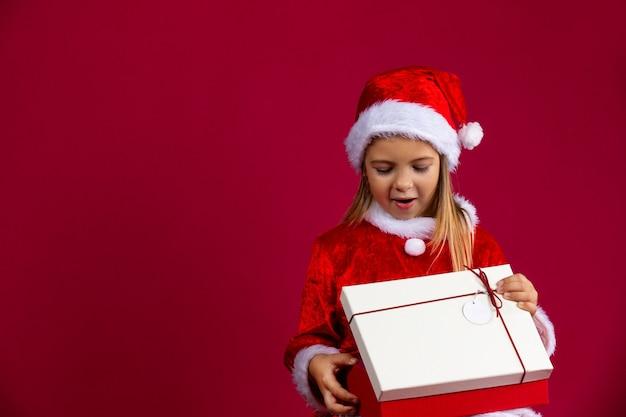 Kleines mädchen in einem weihnachtskleid, das eine weihnachtsmütze mit überraschung trägt, öffnet ein geschenk an einer roten wand mit einem seitlichen leerzeichen.