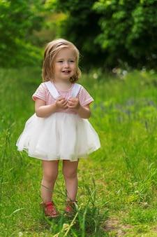 Kleines mädchen in einem weißen kleid mit blonden haaren steht auf einer grünen lichtung und lacht