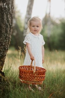 Kleines mädchen in einem weißen kleid mit einem korb im park. schönes baby, das in einen sonnigen garten mit einem korb geht.