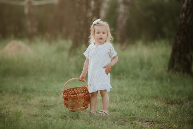 Kleines mädchen in einem weißen kleid mit einem korb im park. schönes baby, das in einen sonnigen garten mit einem korb geht