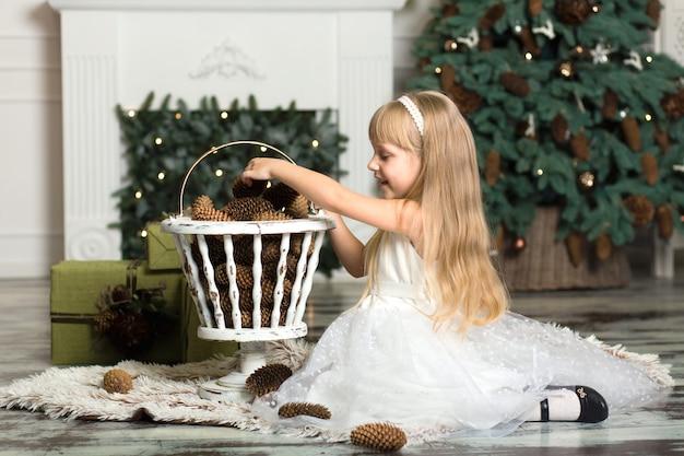 Kleines mädchen in einem weißen kleid spielt mit tannenzapfen