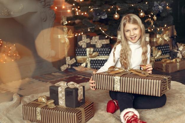 Kleines mädchen in einem weißen pullover nahe weihnachtsbaum mit geschenk
