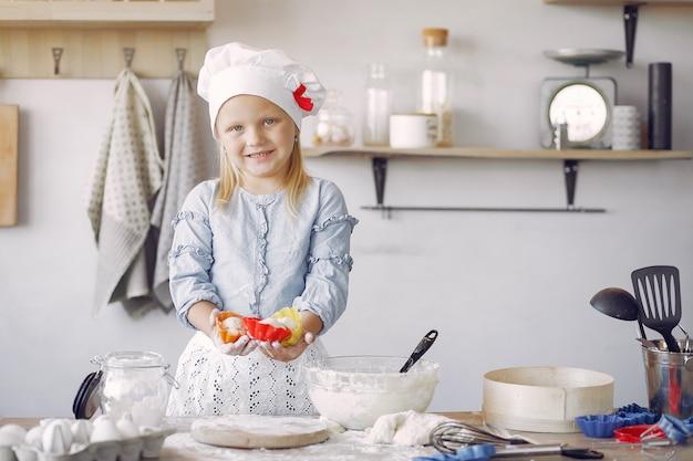 Kleines mädchen in einem weißen schafhut kochen den teig für plätzchen