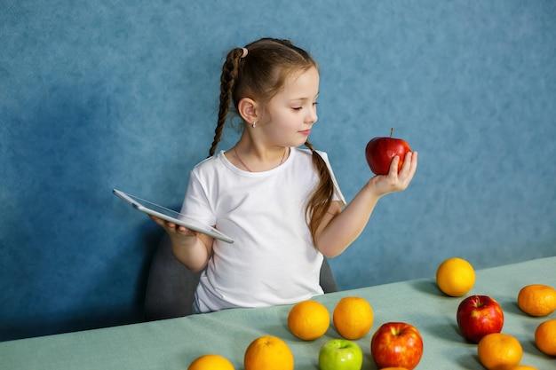 Kleines mädchen in einem weißen t-shirt hält eine tablette in den händen und studiert die früchte