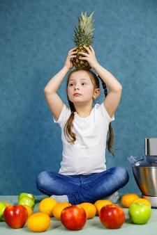 Kleines mädchen in einem weißen t-shirt liebt früchte. sie hält eine ananas in ihren händen