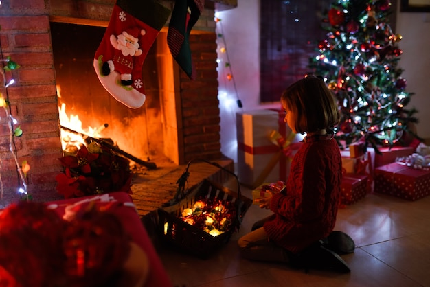 Kleines mädchen in einem zimmer für weihnachten dekoriert
