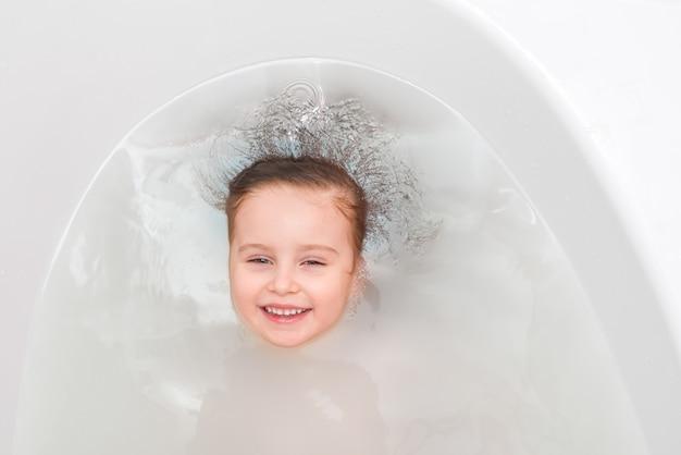 Kleines mädchen in einer badewanne, tauchen, draufsicht