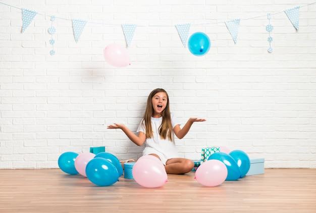 Kleines mädchen in einer geburtstagsfeier, die mit ballonen spielt