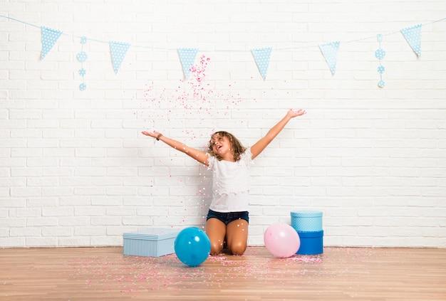 Kleines mädchen in einer geburtstagsfeier, die mit konfetti spielt