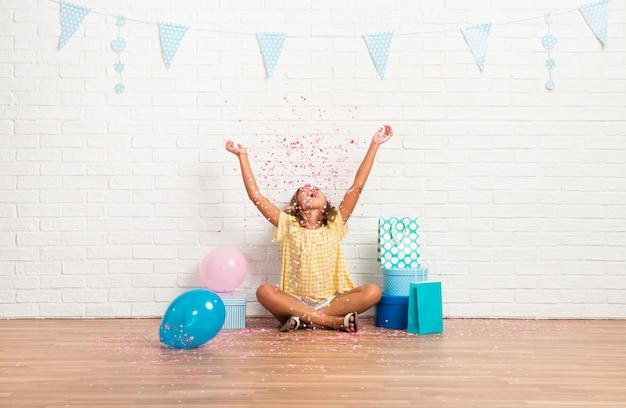 Kleines mädchen in einer geburtstagsfeier, die mit konfettis spielt