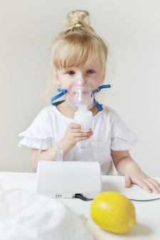 Kleines mädchen in einer maske für einatmungen, einatmung mit inhalator des zerstäubers zu hause auf dem tisch machend, innen-, krankes kind