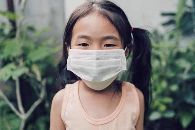 Kleines mädchen in einer medizinischen maske bleiben zu hause