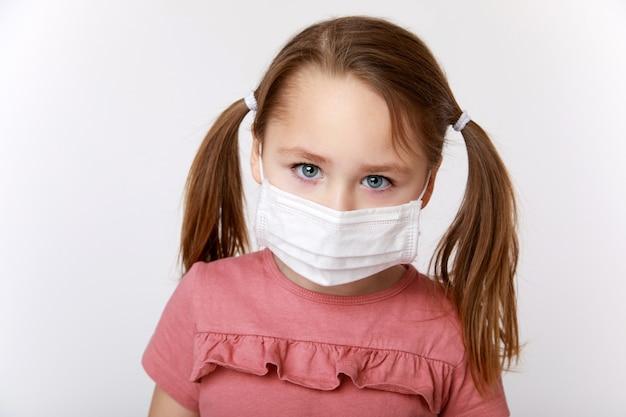 Kleines mädchen in einer medizinischen maske, die vorwurfsvoll schaut