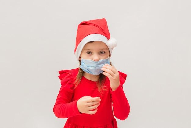Kleines mädchen in einer medizinischen maske in einer roten kappe auf einer weißen wand mit raum für text
