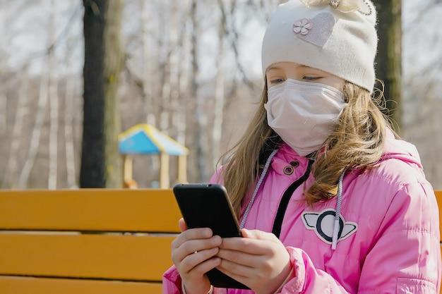 Kleines mädchen in einer medizinischen maske schützt sich vor dem virus, ein mädchen in einer medizinischen maske mit einem telefon in den händen, schutz vor dem coronavirus, covid-19, nahaufnahme