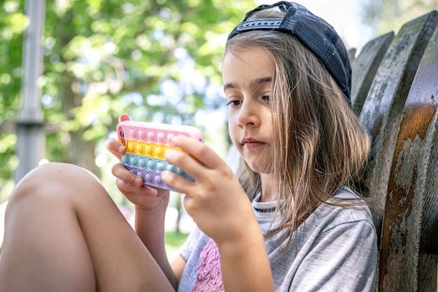Kleines mädchen in einer mütze mit einem smartphone in einer hülle im stil von spielzeug anti-stress-pop it.