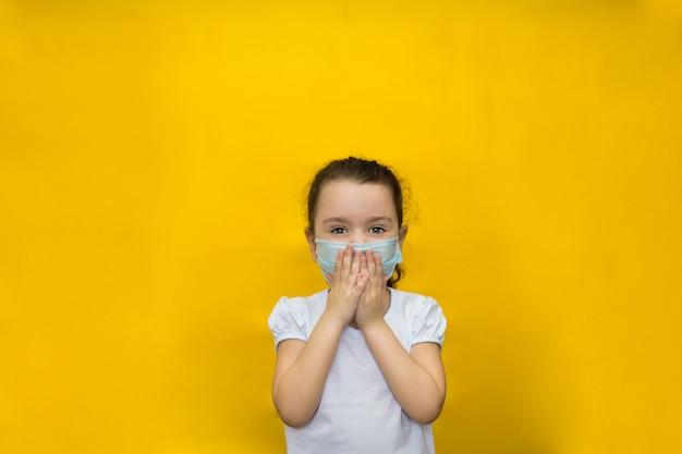Kleines mädchen in einer schutzmaske bedeckt ihren atem mit ihren händen an einer gelben wand. schutz vor coronavirus