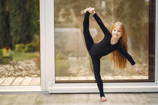 Kleines mädchen in einer schwarzen sportbekleidung ist mit gymnastik beschäftigt