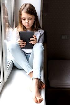 Kleines mädchen in freizeitkleidung sitzt zu hause auf der fensterbank und benutzt das tablet