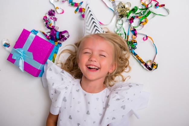 Kleines mädchen in geburtstagskappe lächelnd mit geschenkbox und konfetti