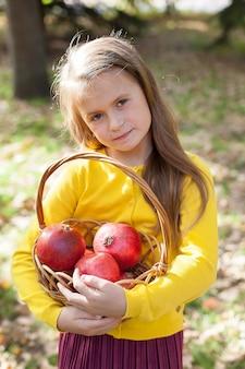 Kleines mädchen in gelber jacke und kastanienbraunem rock steht im park und hält reife granatäpfel.
