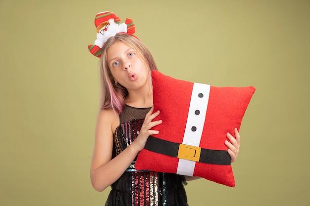 Kleines mädchen in glitzer-partykleid und stirnband mit weihnachtsmann, der ein lustiges kissen hält und die kamera anschaut, überrascht, über grünem hintergrund zu stehen