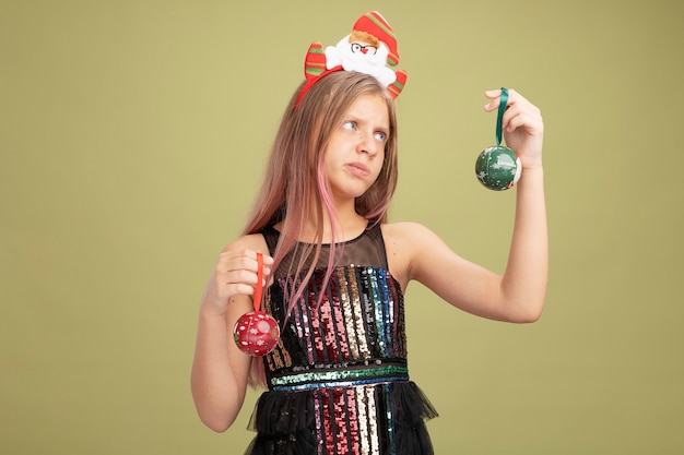Kleines mädchen in glitzer-partykleid und stirnband mit weihnachtsmann, der weihnachtskugeln hält, die verwirrt aussehen und zweifel haben, wenn sie versuchen, eine wahl zu treffen, die über grünem hintergrund steht