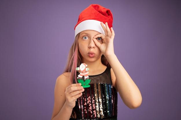 Kleines mädchen in glitzer-partykleid und weihnachtsmütze, das ein weihnachtsspielzeugschild zeigt, das durch dieses schild schaut und in die kamera schaut, die auf violettem hintergrund steht