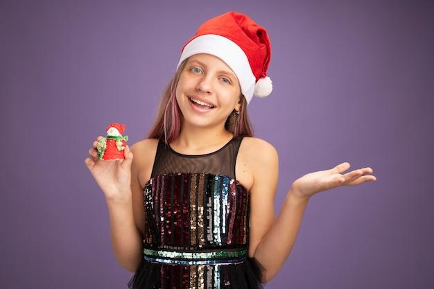 Kleines mädchen in glitzer-partykleid und weihnachtsmütze, das weihnachtsspielzeug zeigt, das in die kamera schaut und mit glücklichem gesicht auf violettem hintergrund lächelt