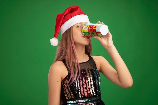 Kleines mädchen in glitzer-partykleid und weihnachtsmütze trinkt aus buntem pappbecher, der über grünem hintergrund steht