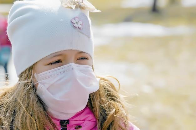 Kleines mädchen in medizinischer maske schützt sich vor dem virus, schutz vor coronavirus, covid-19, nahaufnahme