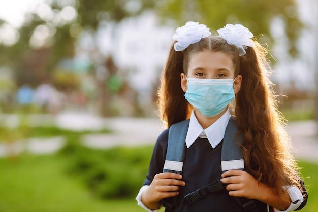 Kleines mädchen in medizinischer maske zurück zur schule. schulmädchen mit medizinischer gesichtsmaske.
