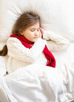 Kleines mädchen in pullover und schal liegend schlafend im bett lying