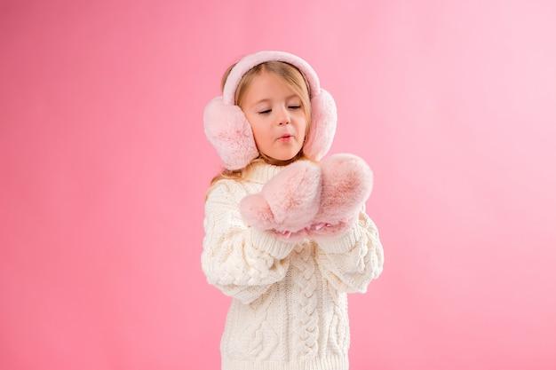 Kleines mädchen in rosa fäustlinge und kopfhörer an einer rosa wand