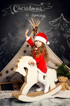 Kleines mädchen in santa kostüm auf einem schaukelpferd ist bereit, die feiertage zu feiern.