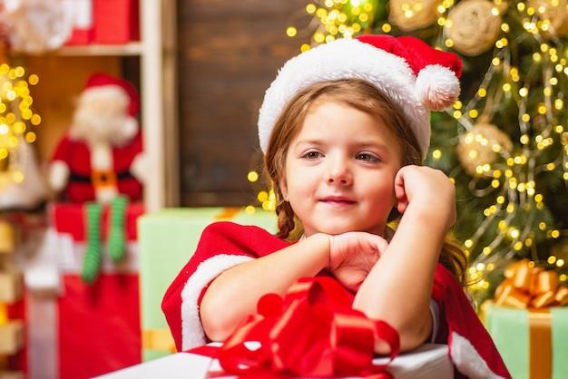 Kleines mädchen in santa kostüm in der nähe eines geschenks drinnen