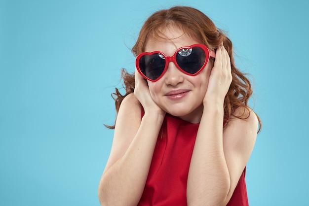 Kleines mädchen in sonnenbrille in form von herzen rotes kleid lockiges haar blau
