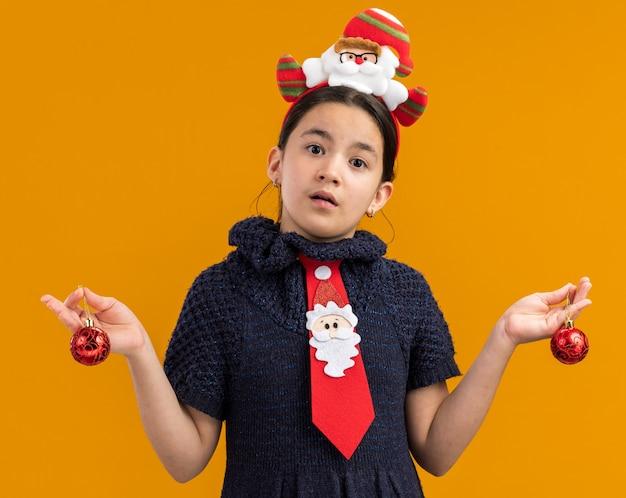 Kleines mädchen in strickkleid mit roter krawatte mit lustigem rand auf dem kopf, das weihnachtskugeln hält, verwirrt, die arme an den seiten über orangefarbener wand stehend auszubreiten