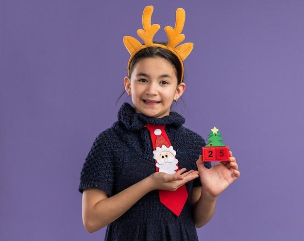 Kleines mädchen in strickkleid mit roter krawatte mit lustigem rand mit hirschhörnern auf dem kopf, das spielzeugwürfel mit weihnachtsdatum hält und mit dem arm glücklich und positiv lächelnd über lila wand steht